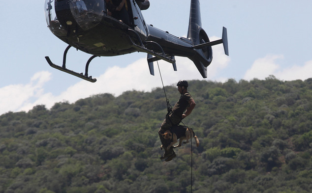 In this photo taken Wednesday, Nov. 26 2014 a handler and his dog abseil from a helicopter, in a simulated exercise showing training at an academy run by the Paramount Group, near Rustenburg, South Africa. The course prepares canine units to find firearms or contraband, track suspects in the undergrowth and abseil in harnesses from helicopters in pursuit of poachers. Dogs and handlers learn to trust each other and fine tune a relationship balancing control and aggression. (AP Photo/Denis Farrell)